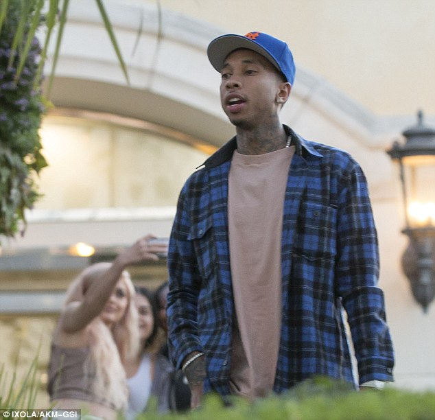 Leaving her to it: Tyga strolled ahead while Kylie continued to take selfies