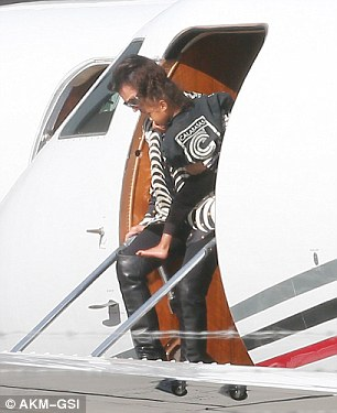 Staying close: Kris kept a tight grip on North as they excited the private jet after touching down in LA from New York