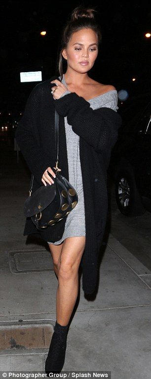 Leggy lady: The M.I.L.F. $ video vixen - who relies on stylist Monica Rose - bared her shoulder in a loose grey mini-dress, black maxi-cardigan, and booties