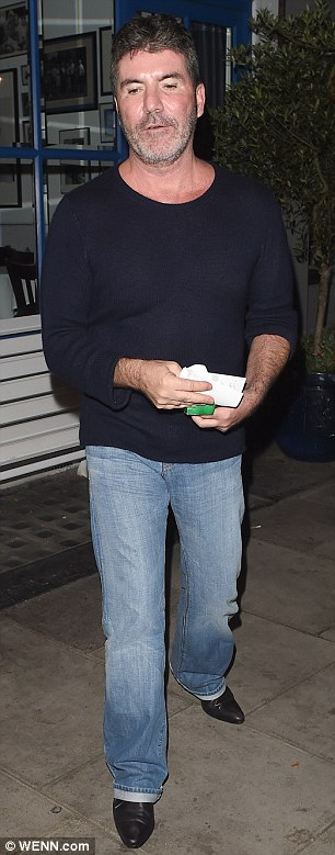 So casual: Simon sported jeans, a dark blue sweater and black shoes for the party