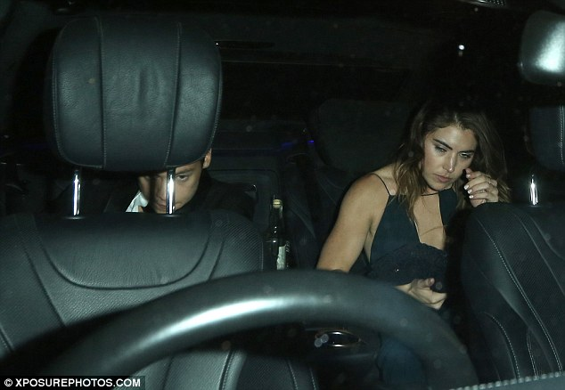 Heads down: Harry was distracted by his phone  in the back of the car