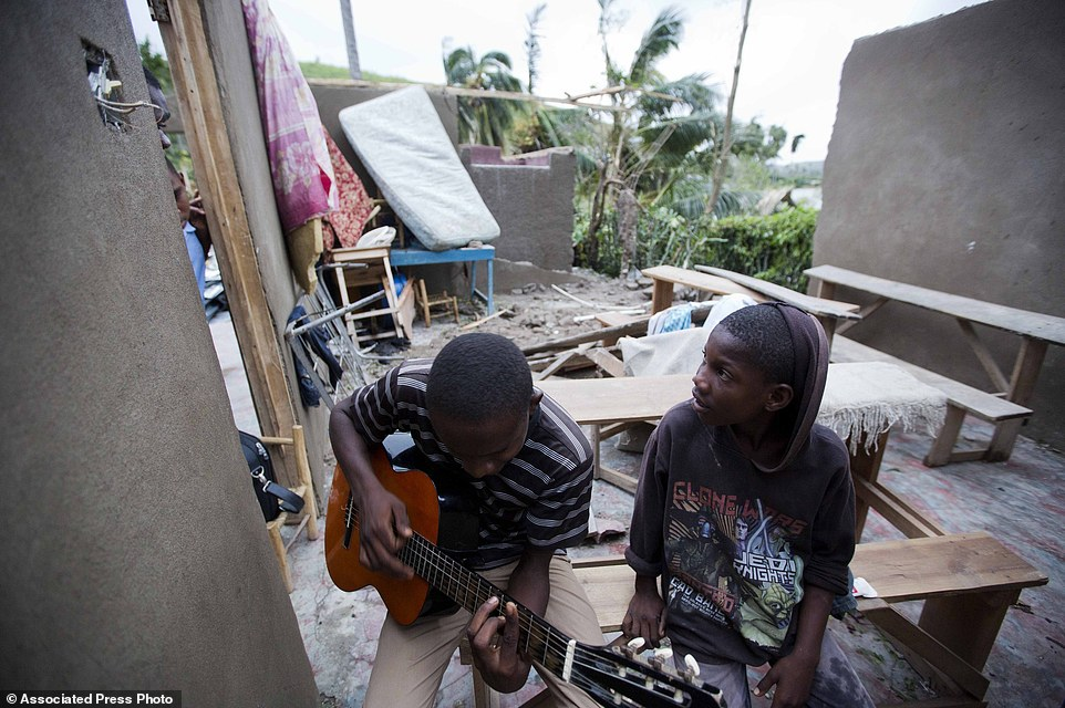 A man sits inside of what is left of his home with his cousin after it was damaged by Hurricane Matthew in Saint-Louis, Haiti, on Wednesday