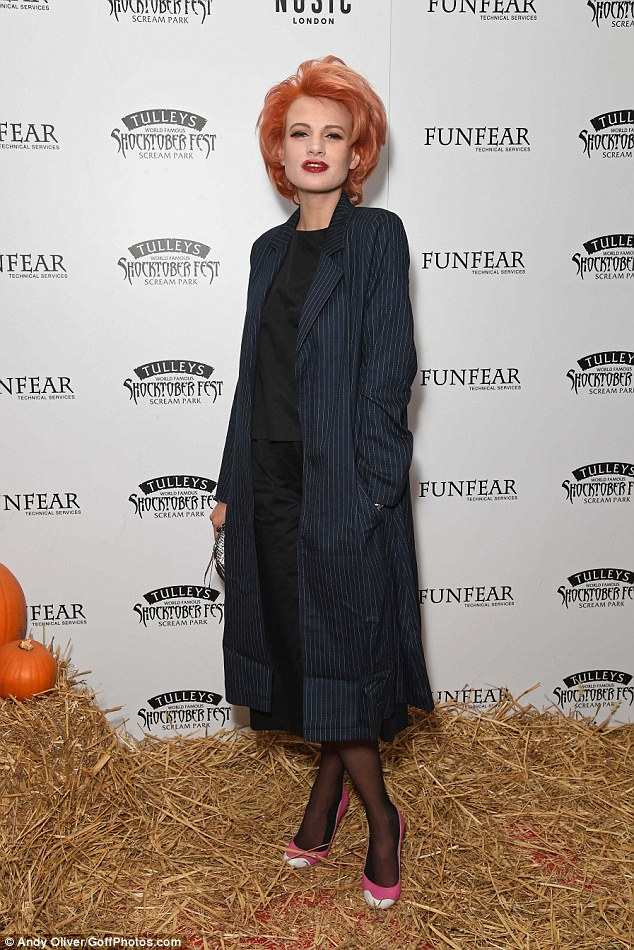 Eccentric: She wore a pin-striped trenchcoat over a black co-ord set which she teamed with some shocking pink heels