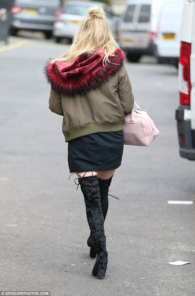 On-trend: The blonde beauty wore her long blonde locks in a stylish half bun and toted a candlyfloss pink handbag over one arm