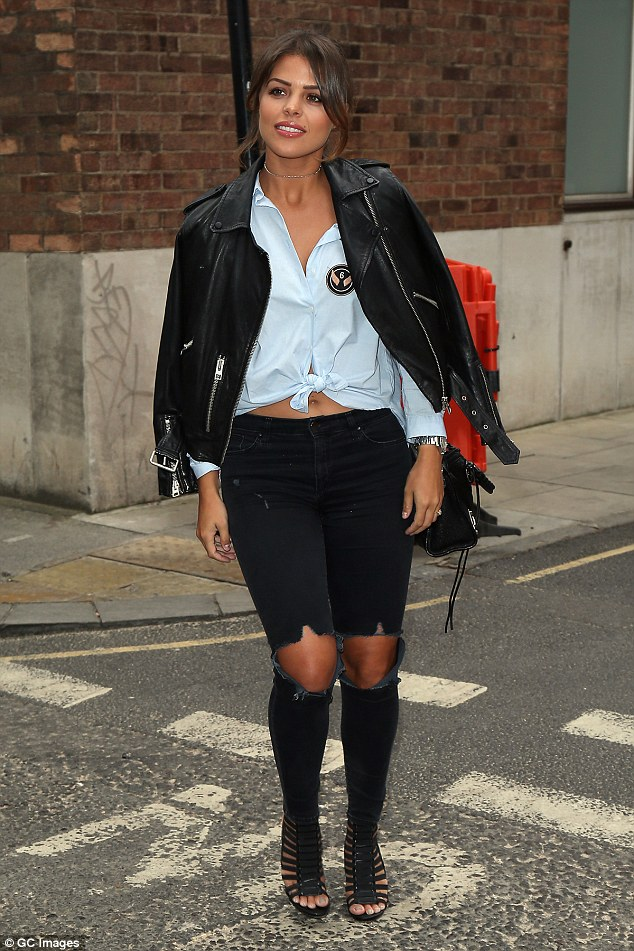 Stylish: Draping a cool biker jacket over her shoulders, the reality star slipped her legs into a pair of skinny black jeans which were ripped at the knees