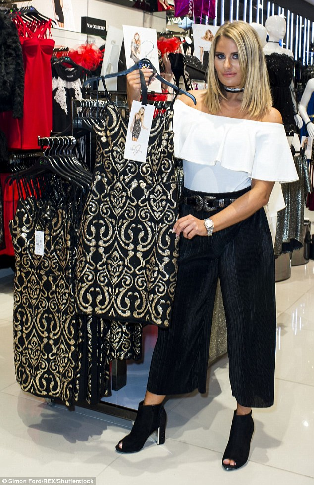 Style queen: The reality star led by example in a white off-the-shoulder top with a large frill tucked into a pair of stylish black trousers secured with an elaborate black and silver belt