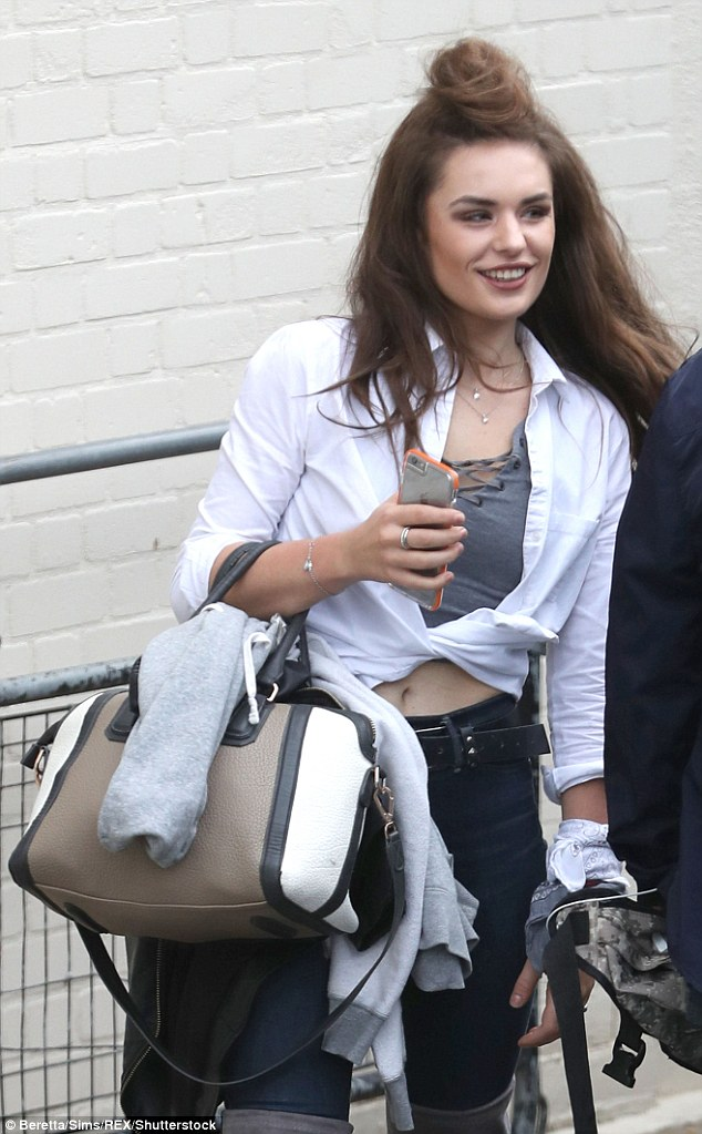 Ready to work: The beauty looked enthusiastic as she juggled a handbag and hoodie on her arm