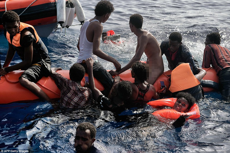 Desperate: Migrants struggled to stay afloat on minimal lift rafts as they waited to be rescued by members of Proactiva Open Arms NGO in the Mediterranean Sea
