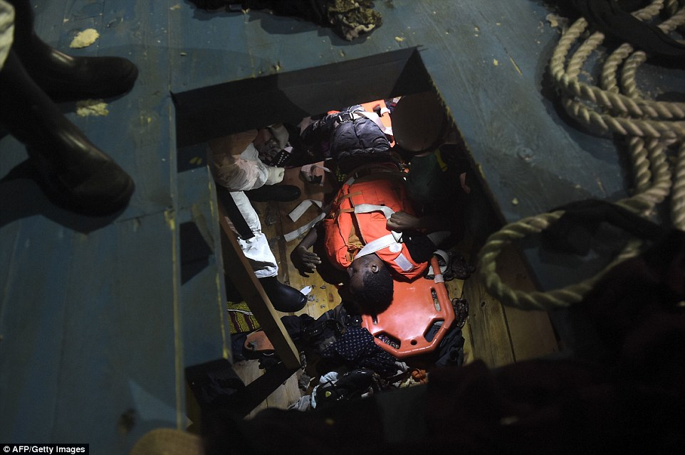 Trapped: A dead body is loaded on to a stretcher inside the hull of the overcrowded boat where at least 22 people died