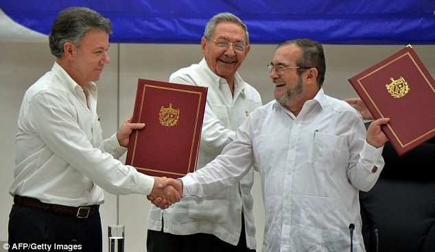 Colombia's President Juan Manuel Santos (left) and Timoleon Jimenez, aka 'Timochenko' (right), head of the FARC leftist guerrilla, shake hands accompanied by Cuban President Raul Castro (C) during the signing of the peace agreement in Havana, Cuba in June this year