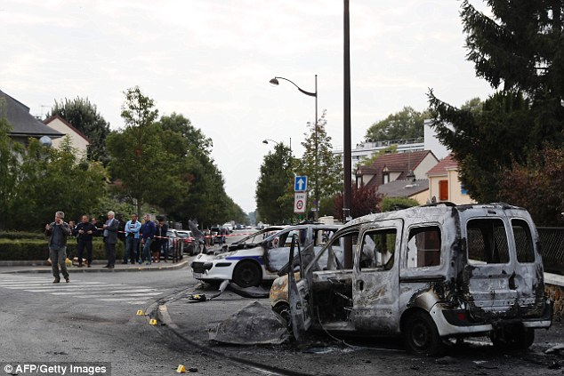 Four French police officers were set on fire after masked thugs pelted their two cars with petrol bombs during a patrol on a notorious housing estate near Paris. Investigators are pictured at the scene