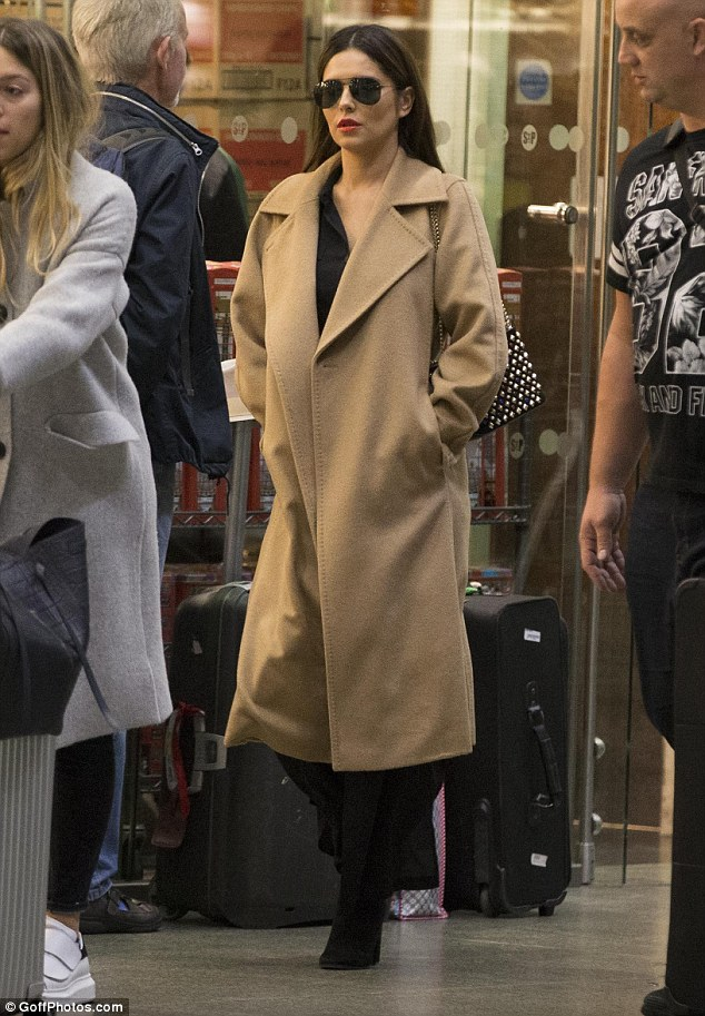 That looks familiar: The singer, 33, sported the same camel coat she wore for her journey to French capital the previous day as she made her way across King's Cross St. Pancras train station