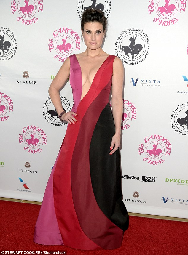 Looking good: Idina Menzel sizzled in a black, maroon, red and pink hued frock that featured a plunging neckline