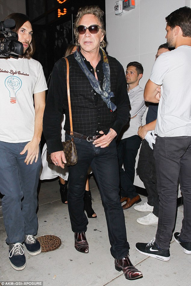 Fighter's purse: Mickey Rourke took his new favourite Louis Vuitton handbag to dinner at Catch LA on Friday