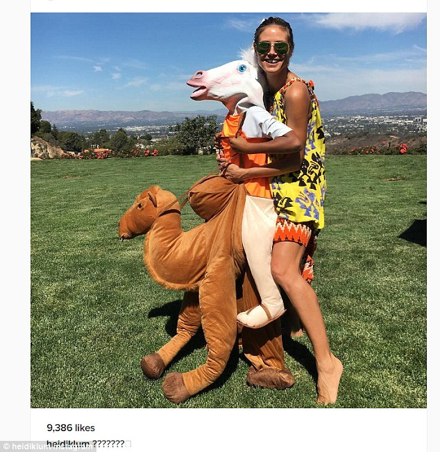 Also Saturday, she shared this playful pic of herself out in a backyard holding onto one of her kids who is sporting a horse's head while standing in the back legs of a camel costume