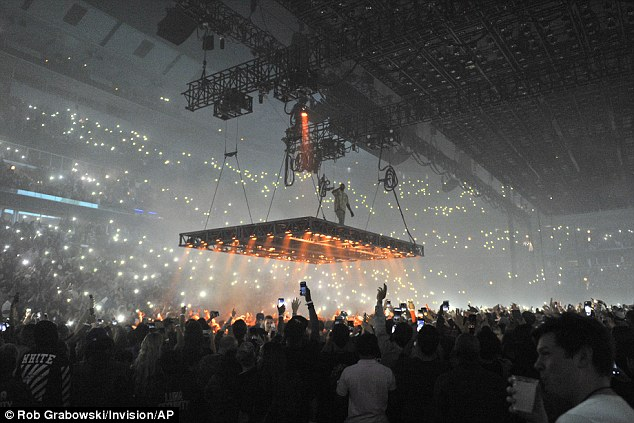 Walking in the air: Harnessed onto his floating stage, Kanye worked a pair of his own high top Yeezys as he slowly moved over the crowd below