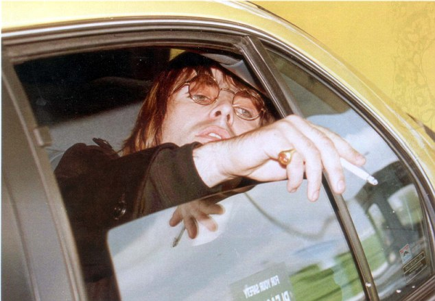 Back in the day: Liam flicks ashes from his cigarette as he leaves Chicago's O'Hare Airport in 1996