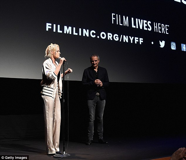 Stand and deliver! Once inside, Stewart continued to demonstrate just how comfortable she was in front of a crowd as she took questions with a microphone in hand beside directorOlivier Assayas