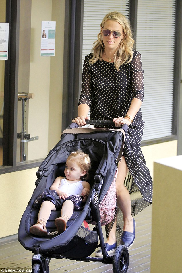 Behaving: The tiny tot, one, sat peacefully in her pram as her model mum pushed her along