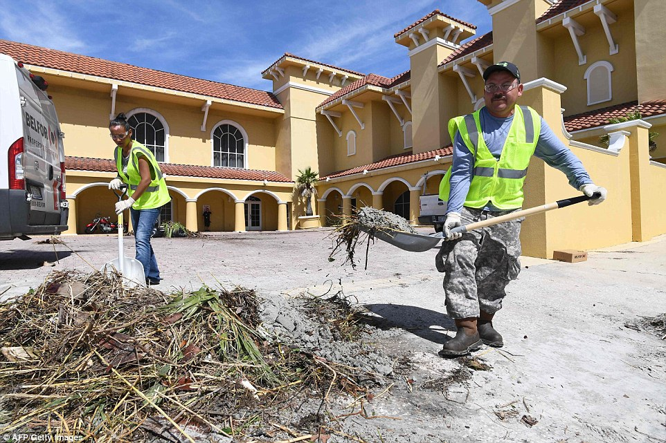 Workers clean debris caused by Hurricane Matthew at a resort in Daytona Beach, Florida on Saturday