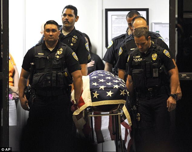 Palm Springs Police Officers carry the body of a fellow officer from Desert Regional Medical Center in Palm Springs to a hearse bound for the coroner's office in Indio, California on Saturday