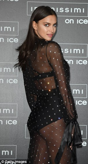 Stunning: Her sleek brunette tresses were tucked behind her ears and fell straight down her back from a middle-parting