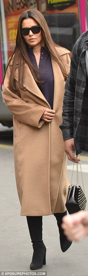 Shying away? Cheryl constantly fastened her coat to keep her shape under wraps