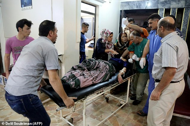 People move an injured woman on a stretcher inside the Al Rahma hospital in the city of Qamishli in the Syrian province of Hasakeh on October 3