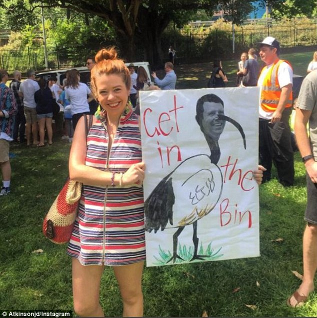 Scores of people have turned up with signs, with many taking a swipe at  Premier Mike Baird