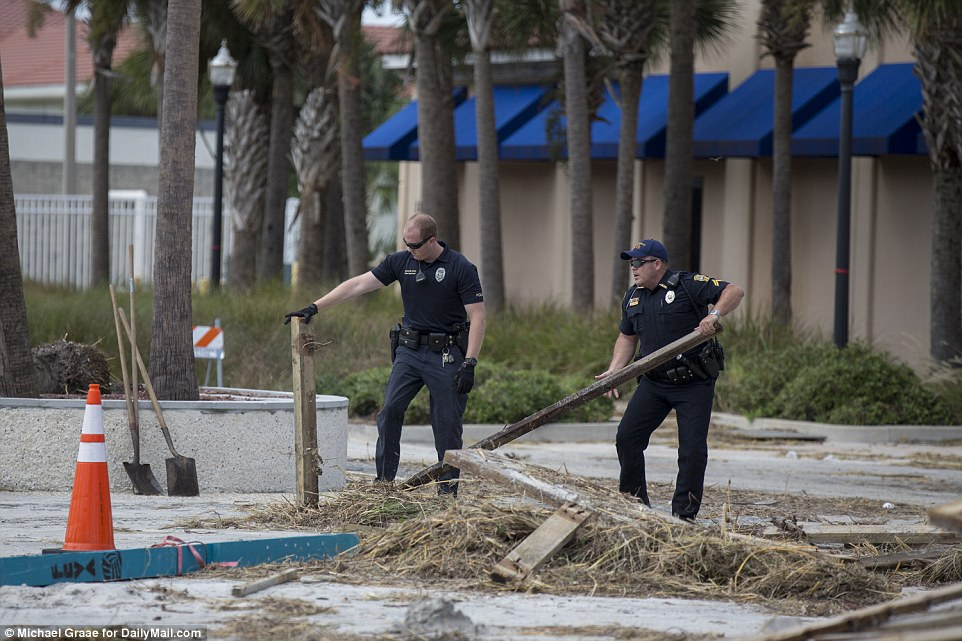 Little damage: Police officers remove debris from a road in Jacksonville as the state capital got back on its feet following Hurricane Matthew
