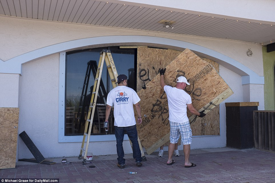 Party time?Employees remove boards from the The Wreck Tiki Bar and Lounge after weathering the storm that passed through