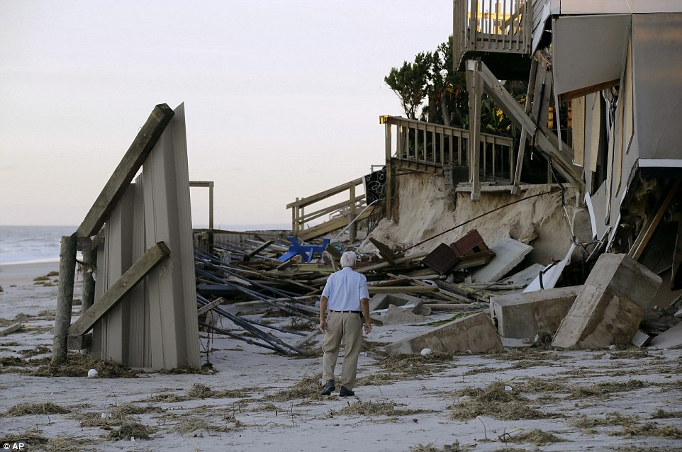 A man surveys the damage done to his neighbor's home in Ponte Vedra Beach on Saturday morning when the state awoke to clear skies