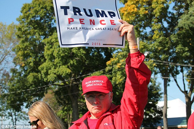 Wisconsin voter Mike Goril holds a 'Trump Pence' sign in the air at the Fall Fest on Saturday in Elkhorn