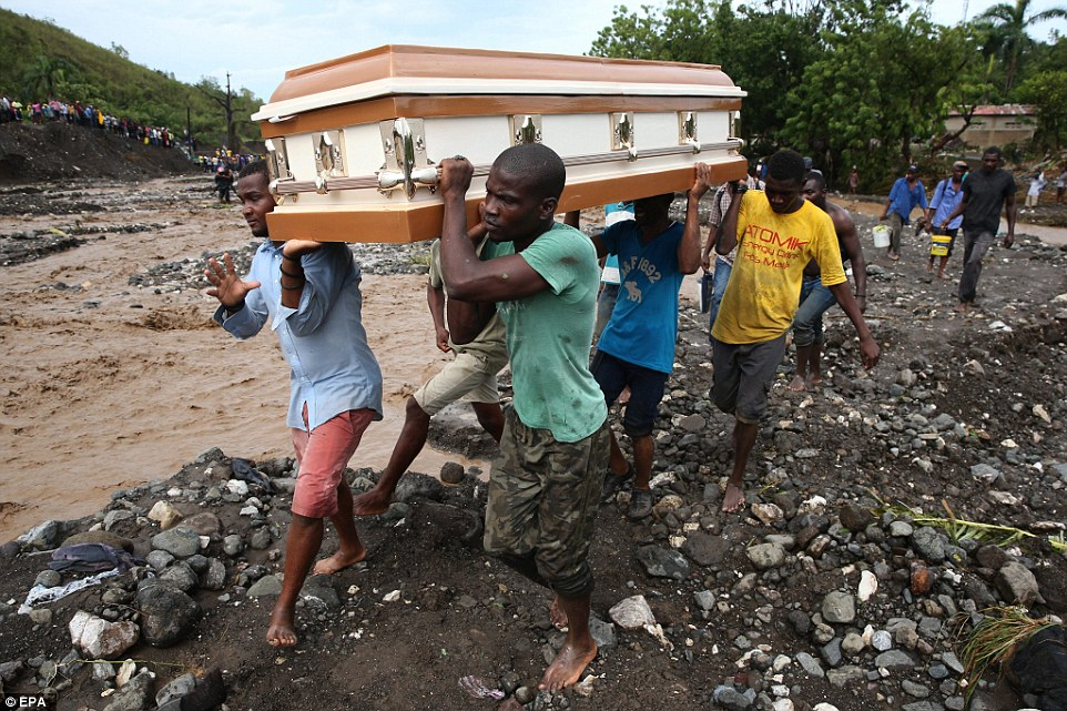 A group of people carry a coffin and try to cross the river La Digue, after the collapse of the only bridge that connects to the south