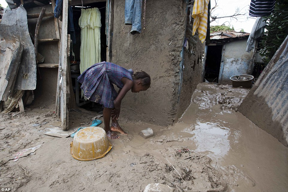 A girl washes mud from her feet after Hurricane Matthew passed in Les Cayes, Haiti, two days after the storm passed