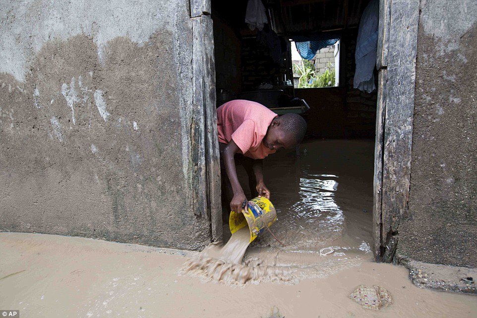 A boy removes mud and water from his completely flooded house in Les Cayes, Haiti