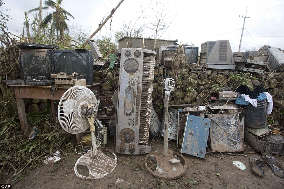 Electronic devices covered in mud stand outside an office destroyed by Hurricane Matthew in Les Cayes