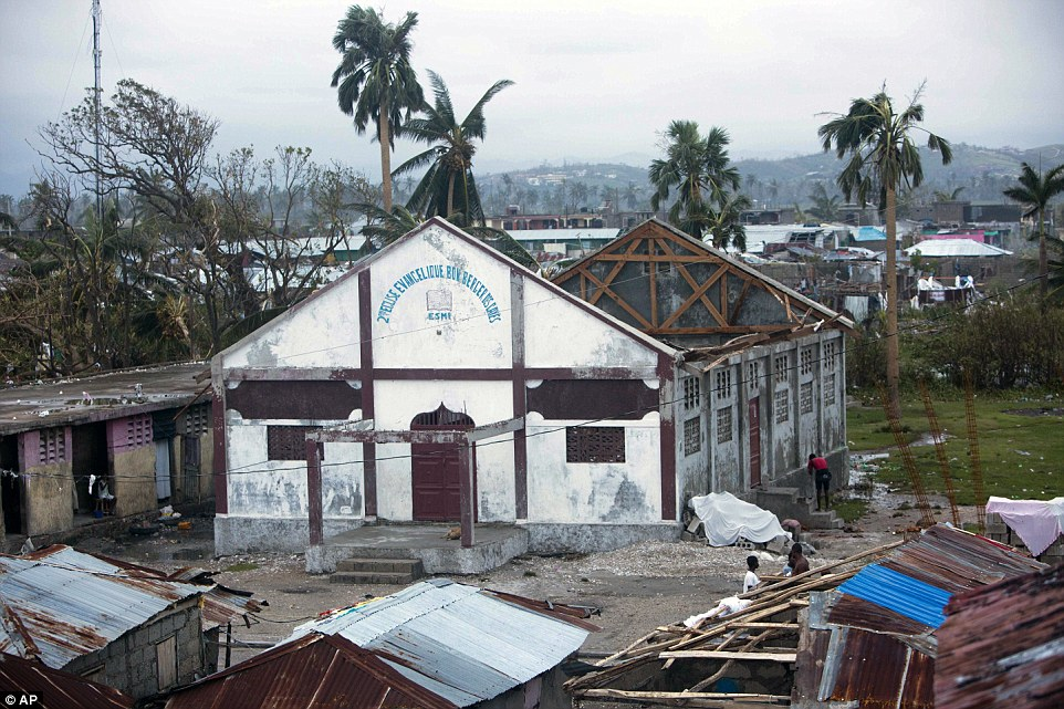 Residents stand near a church that had its roof ripped away by Hurricane Matthew in Les Cayes, Haiti, Thursday, as the repair effort continues