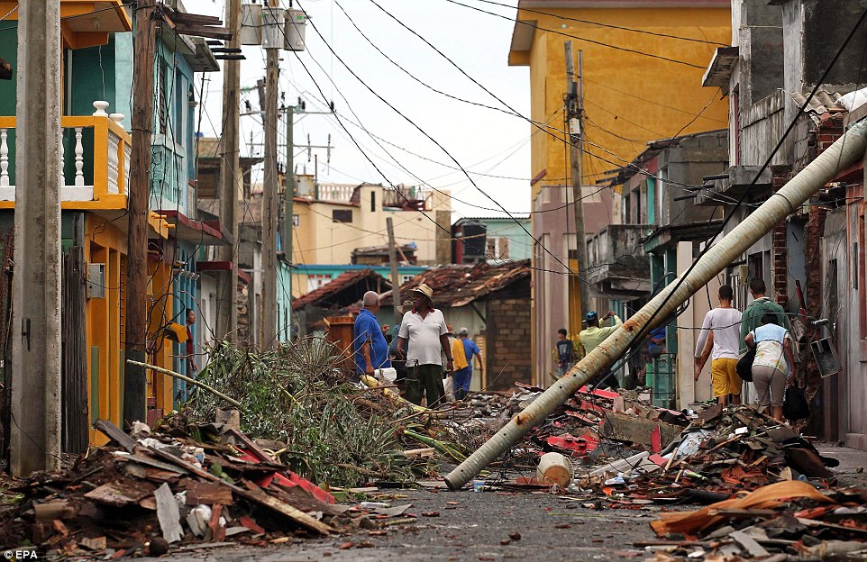 Cubans pick up the pieces on Thursday, following the damage and havoc caused by Hurricane Matthew in Baracoa, Cuba, where the streets are littered with rubble