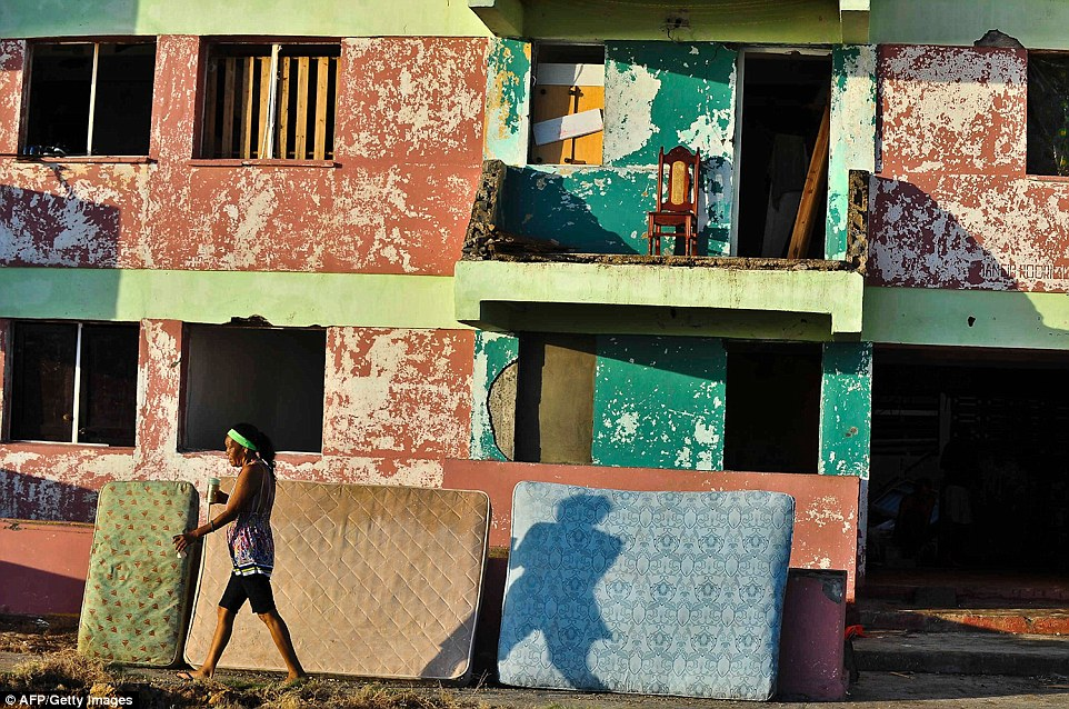 A woman in Baracoa, Guantanamo province, east of Cuba, walks past ruined mattresses. No deaths have been reported in Cuba as of Friday