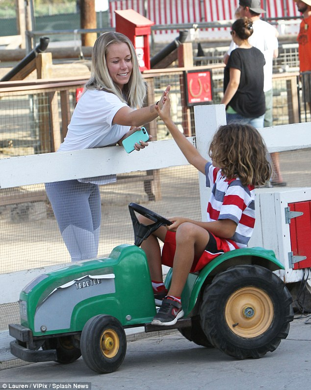 Off he goes: The Kendra star gave her son a high-five as he puttered about on a toy tractor