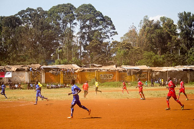 Trying his luck: After a team huddle, the eldest of the Beckham children played alongside Wysa United, a football team based in Kangemi, and managed a header and attempted a tackle