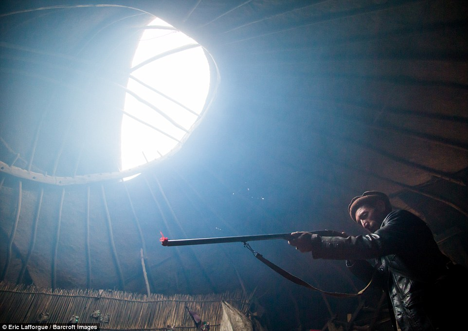 Wakhi nomad man with his gun inside his yurt. The five pillars used in the homes are reflective of the five pillars of Islam