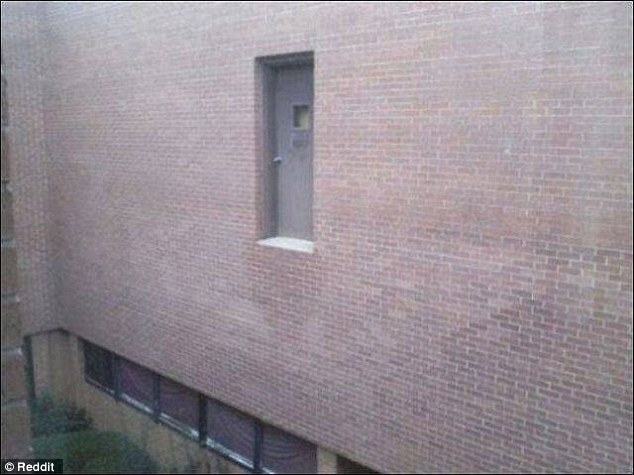 A mysterious door set in a red brick wall leads directly to a dangerously high two story drop