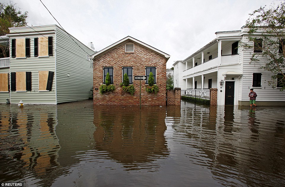 After unleashing days of havoc and fear across the Atlantic coast, Matthew has finally been stripped of its hurricane status. Pictured are flood waters in Charleston, South Carolina