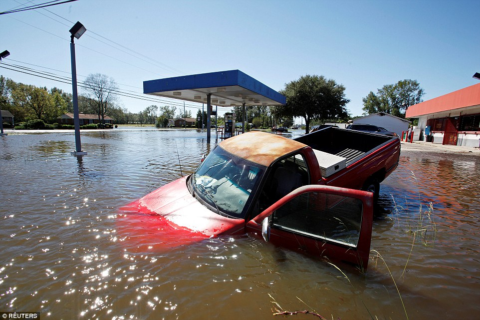 An abandoned truck lies in submerged waters on Sunday afternoon after Hurricane Matthew hit Lumberton