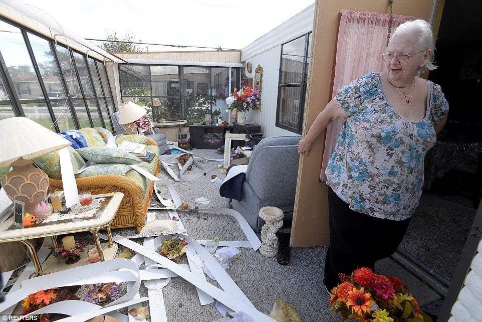Cherie Monroe stands in the sun room of her home in the aftermath of Hurricane Matthew in Port Orange on Sunday