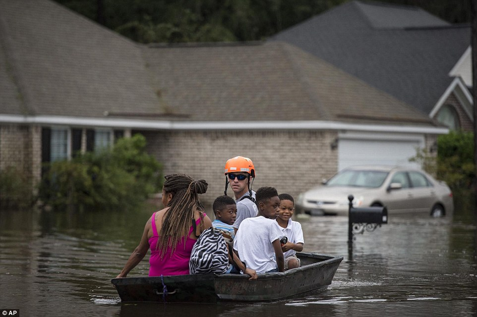 A member of the Pooler Fire Department uses a boat to move residents of homes in a Savannah suburb