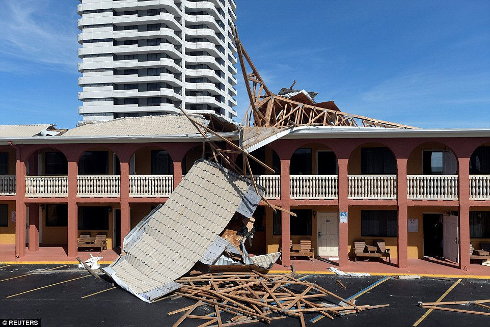 The roof of an adjacent condominium building lies on top of the roof of La Bella Inn in the aftermath of Hurricane Matthew