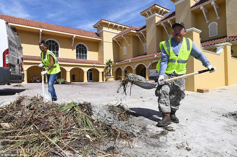 Workers clean debris caused by Hurricane Matthew at a resort in Daytona Beach, Florida on Saturday